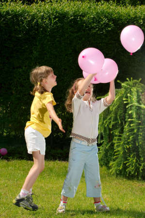 Young girls play balloons