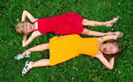 two young girls lie on the grass
