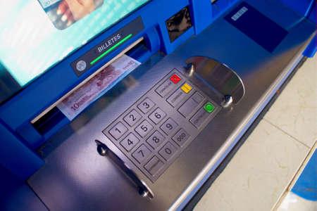 cash dispenser: getting euro paper money at a blue cash dispenser