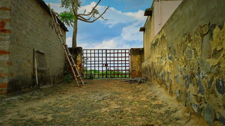 An entry gate of a farm house made with cross cutting saws inside view in blue sky