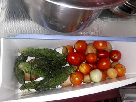 fresh tomatoes, potatoes and bitter gourd in the vegetable section or vessel of a refrigerator