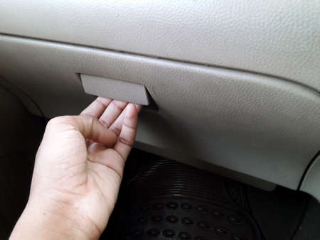 A person opening the glove compartment or document box of car Banco de Imagens