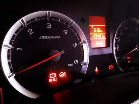 Glowing digital dashboard of a car at night indicating speed, fuel, temperature, power and time and distance traveled closeup