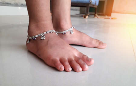 Little Indian kid feet wearing traditional Indian anklet standing on white floor