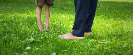 little kid standing or walking on toes in a garden on green grass with help of father / father's day photography
