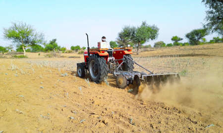 A tractor working in a field agriculture activities