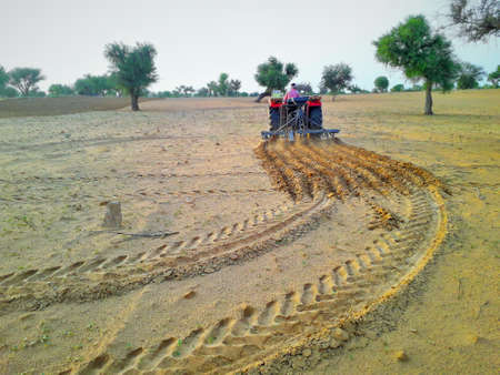 tractor cultivating agriculture land to grow crop in desert area of India Standard-Bild