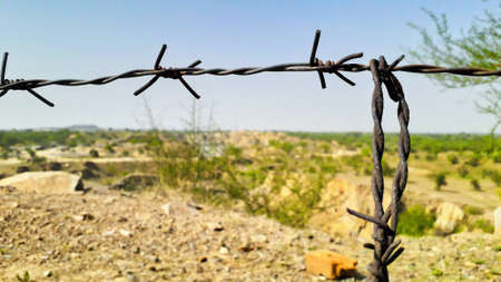 closeup of thorny iron wire for security on plateau land view from a mountain or hill