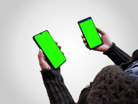 female holding two smart phones mock up in hands with green screen isolated