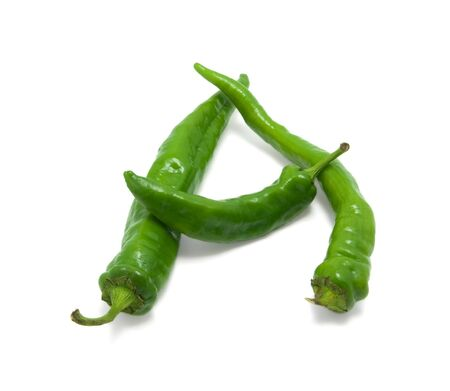 Letter A composed of green peppers on white background photo