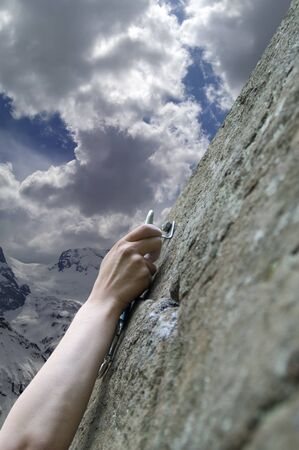 Climbers hand with quick-draws against cloudy mountain photo