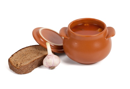 Borsch in clay pot with bread and garlic on white background photo