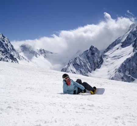 monta�as nevadas: Snowboarder en pista de esqu�. Esqu� Dombay, las monta�as del C�ucaso. Foto de archivo