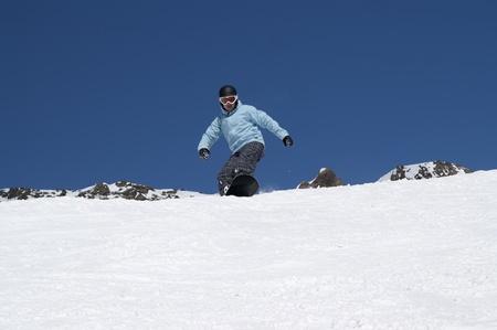 descends: Snowboarder descends a slope