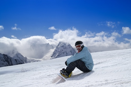 Snowboarder sitting on the snow. Caucasus Mountains, Dombay Stock Photo - 10398455