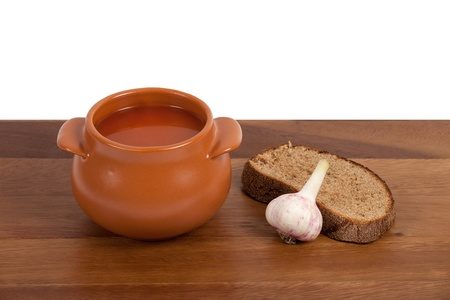 Borsch in ceramic pot with bread and garlic on wooden table photo