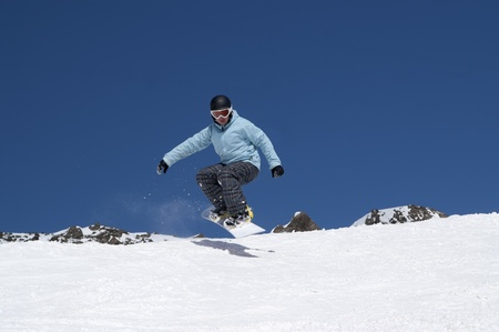 Snowboarder jumping in the snowy mountains photo