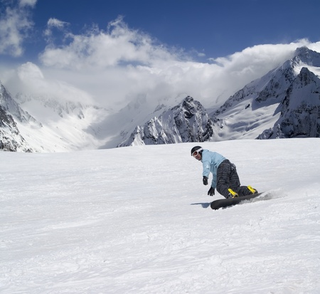 Snowboarder descends a slope in Caucasus Mountains photo