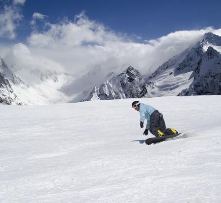 descends: Snowboarder descends a slope in Caucasus Mountains Stock Photo