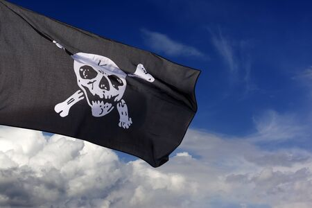 Jolly Roger (pirate flag) against blue sky with clouds Stock Photo - 10836239