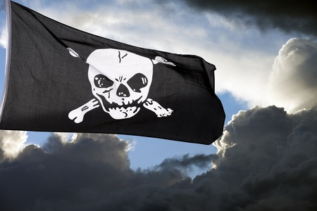 Jolly Roger (pirate flag) against storm clouds Stock Photo - 10836238