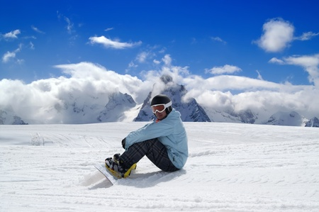 Snowboarder resting on the ski slope. Caucasus Mountains, Dombay