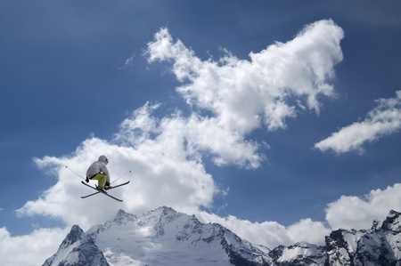 Freestyle ski jumper with crossed skis against snowy mountains Stock Photo - 10899871