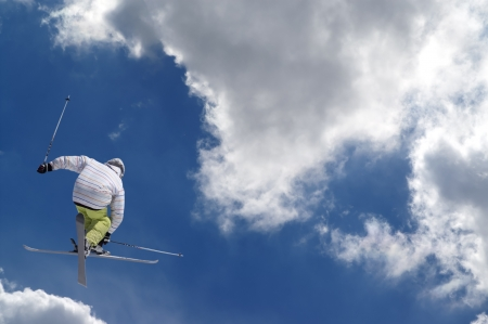 freestyle: Freestyle ski jumper with crossed skis against blue sky with clouds