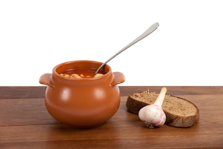 Borsch in clay pot with bread and garlic on wooden table photo