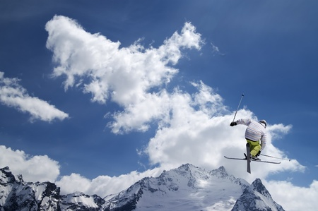 Freestyle ski jumper with crossed skis against snowy mountains  Stock Photo