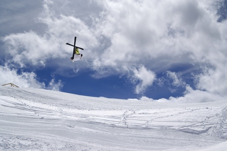 Freestyle ski jumper head over heels with crossed skis against cloudy sky photo