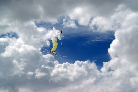 Freestyle ski jumper against blue sky with clouds photo