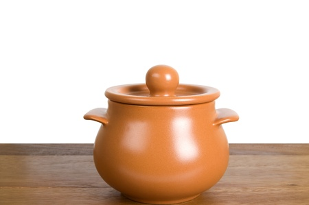 Kitchen clay pot on the wooden board. Isolated on white background photo