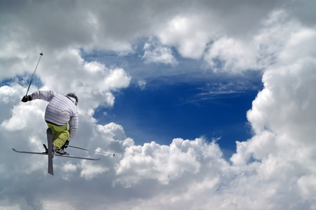 Freestyle ski jumper with crossed skis against blue sky with clouds photo