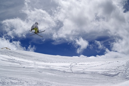 Freestyle ski jumper with crossed skis against cloudy sky  photo