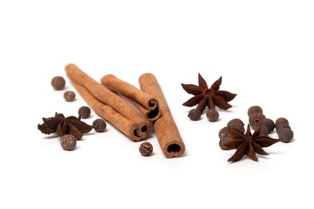 Black peppercorns, anise stars and cinnamon sticks on white background Stock Photo - 12433695