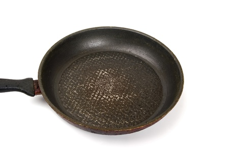 Dirty old frying pan on white background. Top view photo