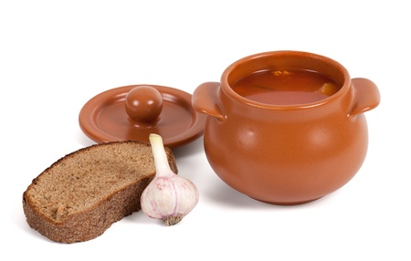 Soup in clay pot with bread and garlic on white background Stock Photo - 13008120