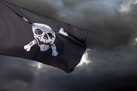 drapeau pirate: Jolly Roger drapeau de pirate contre les nuages ??de temp�te Banque d'images