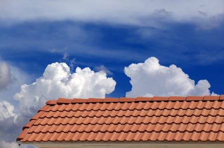 Las tejas y el cielo azul con nubes Foto de archivo