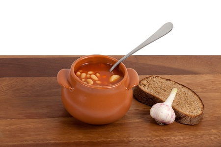 Soup in ceramic pot with bread and garlic on wooden table photo