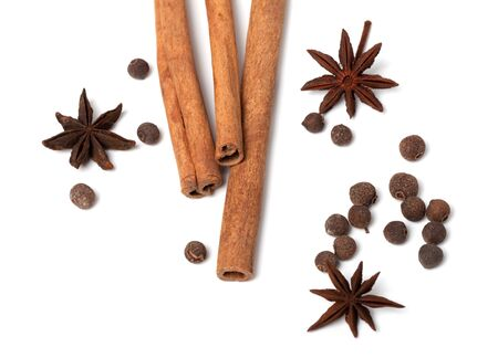 Black peppercorns, anise stars and cinnamon sticks on white background  Close-up view  photo
