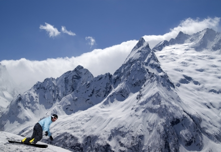 Snowboarder descends a slope in Caucasus Mountains Stock Photo