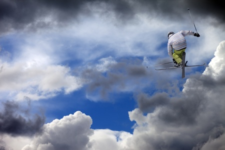 Freestyle ski jumper with crossed skis against cloudy sky Stock Photo - 15928054