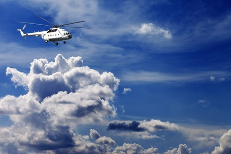 Helicopter in blue sky with clouds photo