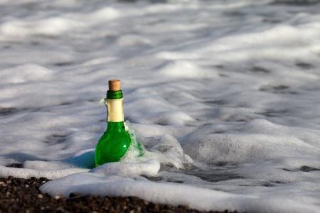 bury: Bottle of wine in sea surf Stock Photo