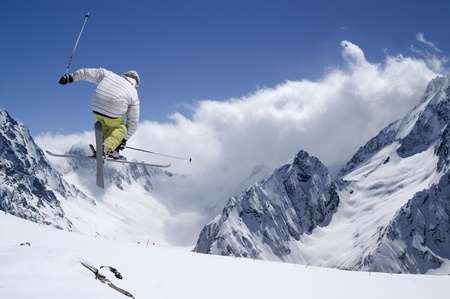 Freestyle ski jumper with crossed skis in high mountains photo