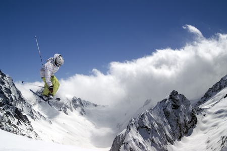 Freestyle ski jumper with crossed skis against blue sky and snow mountains photo