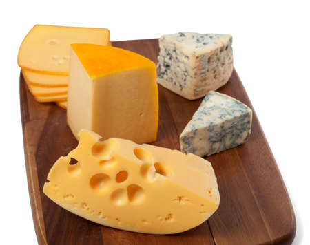 Different types of cheese on wooden kitchen board photo