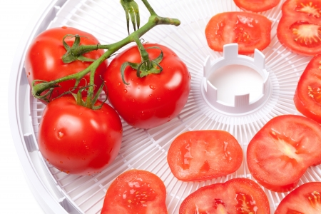 Fresh tomato with water drops on food dehydrator tray photo